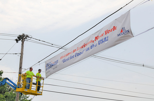 "James Neiss/staff photographerLewiston NY - Lewiston DPW workers Larry Wills and Anthony Mang hang a banner over Center Street after being voted ""Best for Food"" in the USA by Rand McNally's Best of the Road."