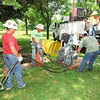 James Neiss/staff photographerNiagara Falls, NY - Members of Nik Wallenda's engineering team, on the ground from left are, Dan Hill, journeyman lineman, Randy Fletcher, general foremen, Justin DeSantis, lineman, and Dennis Morgan, general foreman, install a shoulder block to support the cable and a yoke plate to distribute the line tension on Goat Island at Niagara Falls State Park. Crews started about 10a.m. on Monday setting up Wallenda's wire for his walk across the Niagara Gorge on June 15.