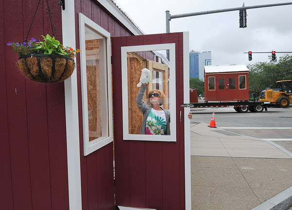 James Neiss/staff photographerNiagara Falls, NY - Kathy Antonucci of Niagara Falls, cleans up a stall that will house Circle Of Life, a gift shop featuring jewelry and handbags, she said. City workers set up the Holiday Market stalls on Old Falls Street that are being repurposed for the June 15, Wallenda Walk activities downtown.