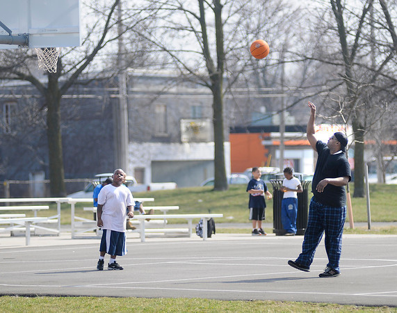 "James Neiss/staff photographerNiagara Falls, NY - Terry Murphy, right, shows his son Terryl Murphy, 7, ""how it's done"" at the Legends Basketball Courts on Saturday."