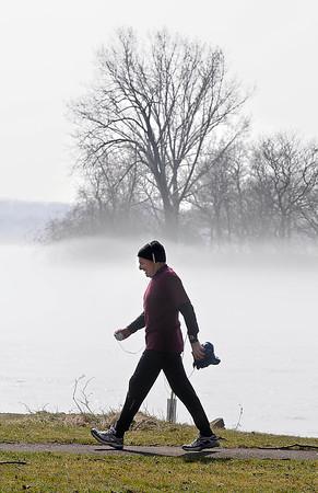 James Neiss/staff photographerNiagara Falls, NY - It was a foggy backdrop for Niagara Falls Attorney Robert Viola as he walks along the upper rapids after a Saturday morning run at Niagara Falls State Park.