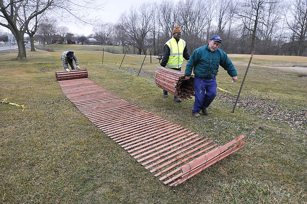 James Neiss/staff photographerNiagara Falls, NY - Hyde Park Golf Course workers, from left, John Overbeck, William Wilson and John Calabro take down the snow fencing at the golf course. The fence saw little snow this winter, but acted as a great wind barrier preventing debris from littering the course, said Wilson.
