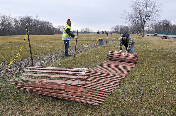 James Neiss/staff photographerNiagara Falls, NY - Hyde Park Golf Course workers, from left, William Wilson and John Overbeck take down the snow fencing at the golf course. The fence saw little snow this winter, but acted as a great wind barrier preventing debris from littering the course, said Wilson.