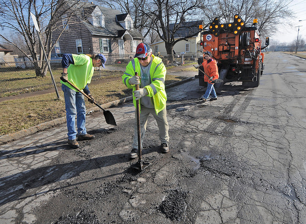 James Neiss/staff photographerNiagara Falls, NY - Pothole Killers: DPW workers, from left, Richard Harvey, Jon Fadel and Toni Manzare fill potholes with cold patch on Kies Avenue.