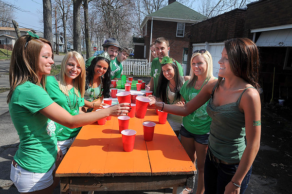 James Neiss/staff photographerNiagara Falls, NY - Niagara University math major Brinna Jones, left, and business major Jes McCoy clink glasses in a salute before playing a drinking game in celebration of St. Patrick's Day during a party on Maple Avenue.