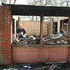 James Neiss/staff photographerGrand Island, NY - A New York State Fire Investigator combs through the remains of a fire at the Beaver Island Golf Course pro shop in hopes of finding a clue as to what started it.