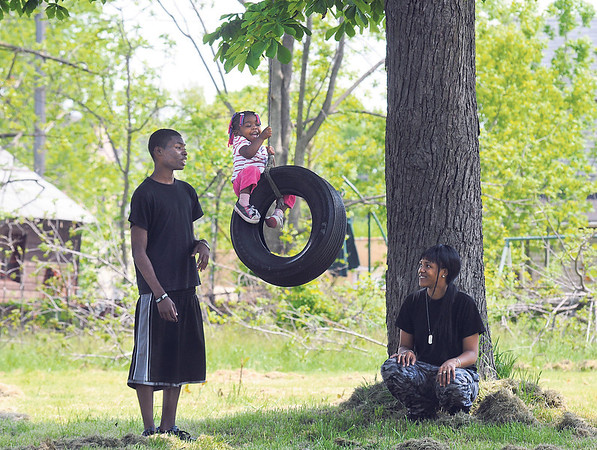 James Neiss/staff photographerNiagara Falls, NY - Anthony Milton took his daughter Axariyah Milton to a local tire swing on Ontario Avenue for a ride. Family friend Santina Hallman, right, said she used to swing on it, because her grandfather hung it there over 20 years ago.