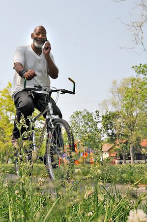 James Neiss/staff photographerNiagara Falls, NY - Greg Davis is surrounded by tall grass as he rides his bike through Gluck Park.