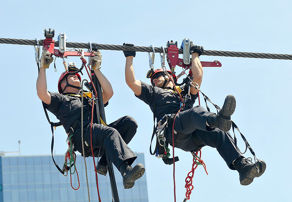 James Neiss/staff photographerNiagara Falls, NY - High above Seneca Plaza Niagara Falls, Ontario, firefighters Scott Wilkinson, left, and Brandon Fife, train with with the  Zip Rescue trolley system, in preparation for Nik Wallenda's walk across the Niagara Gorge. The first responders, said it's a secondary system to what organizers have in place.