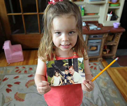 James Neiss/staff photographerNiagara Falls, NY - Young Emma Neville, 2, holding a photo of her siblings Peter, 8, and Rose, 14, with their father Peter Neville, didn't get a chance to know him. Peter Neville was killed in an industrial accident at Norampac. Saturday is the two-year anniversary of his death and his wife Mara Slipko-Neville, is still trying to get someone at the federal level to help her change the rules regarding workplace safety.