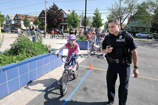 James Neiss/staff photographerNiagara Falls, NY - Niagara Falls Police Officer Angelo Berti watches Jessica Fey, 10, as she keeps her bik between the lines at a Bike Rodeo sponsored by the NFPD at the Niagara Street School.