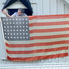 James Neiss/staff photographerLewiston, NY - Paul Fitzpatrick looks for a hook to hang his historic 48 star flag in front of his Niagara Street home on Memorial Day in Lewiston. Fitzpatrick, said the flag was handed down by the previous homeowner.
