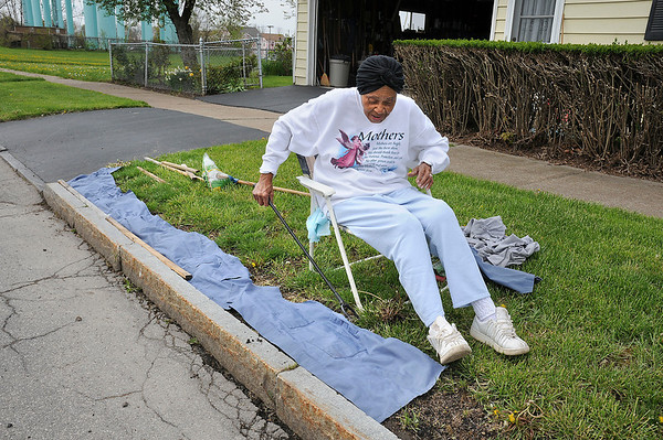 """James Neiss/staff photographerNiagara Falls, NY - Hattie Lowery doesn't let a hip replacement keep her from taking care of a little yard work in front of her Tennessee Avenue home. Lowery was placing old cloth strips over newly seeded grass. """" You do with what you have and do it till you can't no more,"""" she said."""
