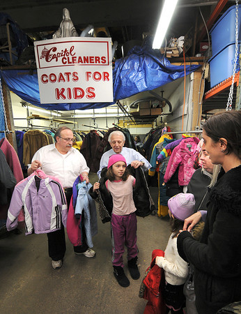 James Neiss/staff photographerNiagara Falls, NY - Russ and Joe Petrozzi, owners of Capital Cleaners on Main Street, help little Isabelle Rivers, 10, try on a coat during the Coats For Kids giveaway on Saturday.