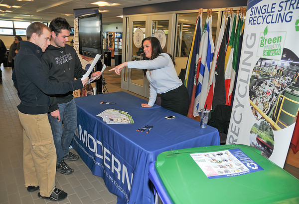 James Neiss/staff photographerNiagara Falls, NY -  Niagara University students Brody Adams and Jonathan Hibbard talk to Joleigh Washuta, with Modern Corp. about recycling at the Gallagher Center, where this, and other booths were set up to educate attendees on how to live more environmentally friendly on America Recycles Day.