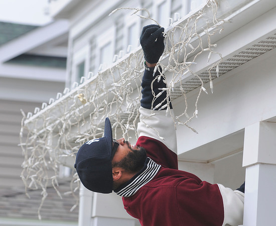 James Neiss/staff photographerNiagara Falls, NY - Mark Robinson works the angles to get the length of his Christmas lights just right on the gutter of his Calumet Avenue home.