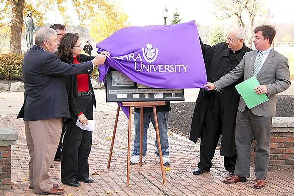 Photo by Brian Rock, Niagara UniversityBrian Merrett, C.E.O. of the 1812 Bicentennial Legacy Council, Arlene White, executive director of the Binational Tourism Alliance, Dr. Thomas Chambers, chair of Niagara University's history department, and the Rev. Joseph L. Levesque, C.M., NU president, unveil a commemorative plaque for the Niagara University 1812 Bicentennial Peace Garden. The garden commemorates the 200 years of peace between Canada and the United States following the War of 1812.