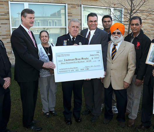 James Neiss/staff photographerNiagara Falls, NY - Niagara Falls Police Superintendent John Chella, accepted a check for $3500 from the Niagara Sikh Association for Lt. Brian Murphy, a wounded Oak Creek, Wisconsin, police officer who came to the rescue of other members of the community during a temple shooting there. From left are, Mayor Paul Dyster, Ranjeet Bambrah, Superintendent John Chella, Sam Bambrah, Hardeep Minhas, Dr. Surjit Singh and Lakhwinder Gill.