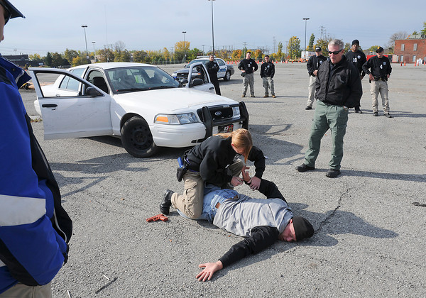 James Neiss/staff photographerNiagara Falls, NY - Niagara County Law Enforcement Academy cadet Felicia DeGroot subdues a felony suspect, played by Niagara Falls Police Officer Mike Corcoran, as NFPD Officer Dan Bird, right, observes. The cadets were playing out a felony traffic stop scenario as part of an Emergency Vehicle Operator Course, or EVOC for short, in Niagara Falls.