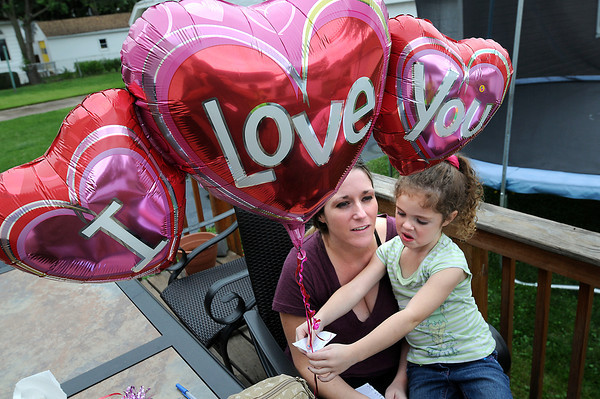 James Neiss/staff photographerNiagara Falls, NY - Long time family friend Lisa Nicologg helps Loretta Gates daughter Mariah Martin, 5, tape drawings and messages for her mother to a balloon they planned to launch.