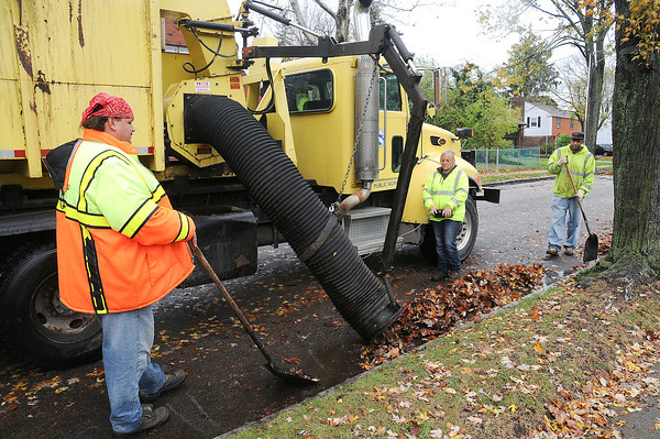 James Neiss/staff photographerNiagara Gazette, NY - Niagara Falls DPW workers, from left, John Soro, Jeanine Harvey and Willie Taul, use a leaf sucker to pick up leaves on Delancey Road in Deveaux.