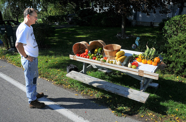 James Neiss/staff photographerRansomville, NY - Bill Leonard of Dickersonville Road checks out his fully stocked roadside vegetable stand near the corner of Balmer Road. Leonard, said he's been gardening for over 20 years and for the last three, has been selling the overflow to the public.