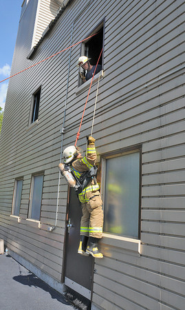James Neiss/staff photographerWheatfield,  NY - With the help of Training Captain Sam Fasciano, top, Niagara Falls firefighter Frank Eugeni Jr. dangles from a second story window after hooking up his SCOTT EZ-Scape Firefighter Self-Rescue Accessory at the Wheatfield Training Facility on River Road in Wheatfield. The hook and break system is meant to be used as a last resort and all firefighters who enter buildings will eventually be trained to use them.