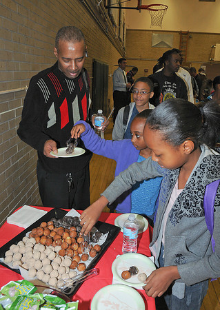 James Neiss/staff photographerNiagara Falls, NY - Willis Walker is served some doughnuts from his grandchildren Carmen Timmons, 9 in 5th grade, Jazmin Hemphill, 7 in 2nd grade, and Patrick Colvin, 11 in 5th grade, during breakfast at Maple Avenue Elementary. The Niagara Falls School District has joined in the State-wide event that encourages fathers and men of significance in the lives of children to take that special child to school on Thursday.