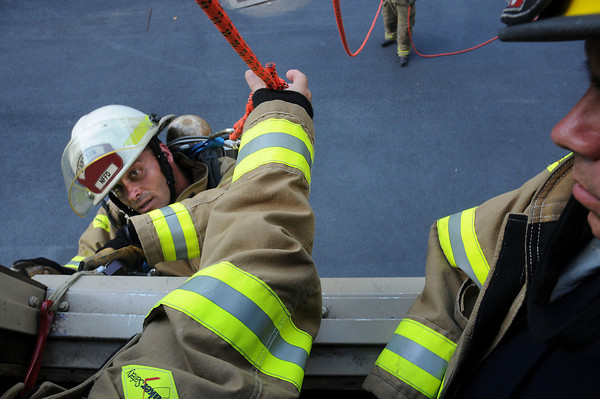 James Neiss/staff photographerWheatfield,  NY - Niagara Falls Fire Department Training Captain Sam Fasciano, demonstrates the use of a SCOTT EZ-Scape Firefighter Self-Rescue Accessory by hooking a window ledge and rolling out the window. A strap with a hand brake made for an easy descent.