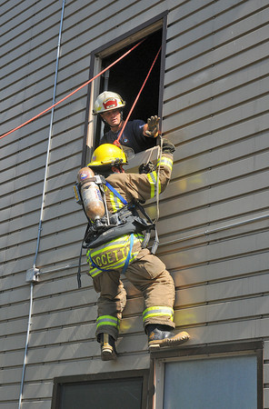 James Neiss/staff photographerWheatfield,  NY - With the help of Training Captain Sam Fasciano, left, Niagara Falls firefighter Pat Accetta dangles from a second story window after hooking up his SCOTT EZ-Scape Firefighter Self-Rescue Accessory at the Wheatfield Training Facility on River Road in Wheatfield. The hook and break system is meant to be used as a last resort and all firefighters who enter buildings will eventually be trained to use them.