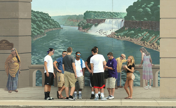 James Neiss/staff photographerNiagara Falls, NY - Niagara University students out for a  bit of Labor Day holiday shopping blend in with the mural at the Fashion Outlets of Niagara Falls on Monday.