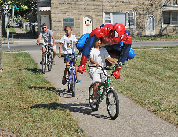 James Neiss/staff photographerNiagara Falls, NY - Antonnio Passauer, 10, shares his bicycle with a super hero friend he said was blowing down the street in the 1600 block of Ferry Avenue. He and his sister Keyona Lamar, 8 and grand father George Magliazzo were heading home after a bike ride.