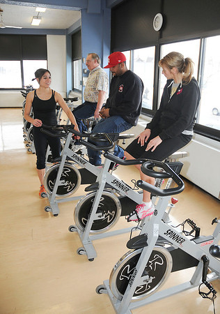 James Neiss/staff photographerNiagara Falls, NY - Group Exercise Instructor Katarina Manuse gives guests, from left, David Bucko and Krystopher Stoner Sr., both of Niagara Falls and Alisa Talarico of Lewiston, a demonstration of the spinning equipment during an open house at the Niagara Falls Branch of YMCA Buffalo-Niagara.