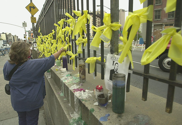 010918 WTC/yellow ribbons--dan cappellazzo photo--A NY resident reads notes attached to hundreds of yellow ribbons in rememberance of those who lost their lives and their families at the WTC tragedy. The ribbons are tied to a fence on Canal street near Verick, mere blocks from the WTC site.