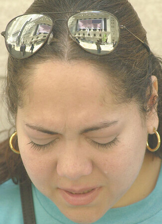 010917 WTC/wall street cry--dan cappellazzo photo--An  American flag that hangs on the front of the NYSE building is reflected in the glasses of a woman crying in front the historic landmark that opened it's doors Monday for trading.