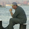010913 NYC/ferry capt.--dan cappellazzo photo--an unidentified ferry worker sits on the end of the boat after a long day of  taking workers and supplies across the Hudson river from NJ to NY to the rescue effort at the WTC sight.