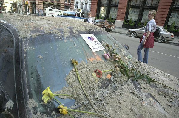 010916 WTC car wreck--dan cappellazzo photo-- Wrecked by the collapse of the twin towers, flowers and a God Bless America note grace a car windshield on Hudson Street, 6 blocks from ground zero.