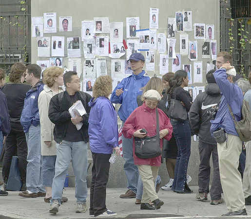 010914 NYC/missing persons wall--dan cappellazzo photo--NYC residents look congragate at a building corner at Lexingtion and 26th ave, in Manhatten, where a make shift wall is set up for people missing in the WTC tragady.