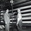 Plant superintendent D. G Thompson (left) talks to workman Arthur Blanchette of General Electric while standing in front of some flying bazooka barrels which have just come out of the oven where their skin is hardened. This oven is similar to those used in peacetime to bake the finish on Refrigerators. The flying bazookas mounted on Thunderbolt fighter planes have wreaked havoc on the Germans in France and the Japanese in the India-Burma-China theater of operations. September 1944.