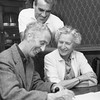 Norman Rockwell signs the charter application for the Southern Berkshire chapter of SANE Nuclear Policy Inc. with Miss Molly Punderson Rockwell (right) and William Gibson in the background, October 19, 1961. Photo is out of focus