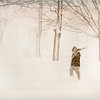 A boy with a snow shovel hikes through the snow, undated. Photo by Michael Miller.