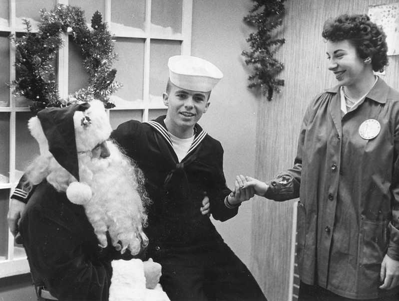 Christmas liberty for sailor Leland Drake of Springside Avenue at England Brothers, December, 1959. Barbara Belcher, in charge of the photo-with-Santa concession holds his hand. Donald Fletcher of Cheshire portrays Santa Claus. Photo by William Tague