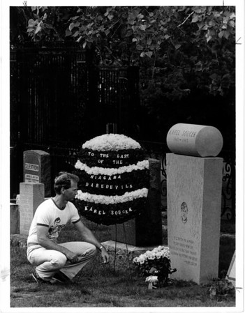 "Niagara River - Stunters<br /> George Rinehart, personal apperance manager for Karl Soucek, places a wreath, pays respect at grave in Drummond Hill Cemetary, Niagara Falls, Ontario. ""Anniversary week"" for Soucek going over the falls in a barrel last 7/2/1984.<br /> Photo - By Tim Johnson - 7/6/1985."