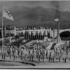 Olympics - 1980 Winter Olympics<br /> The adirondack Mountains soar above the Olympic flame and he festive ceremonies at the opening of the Winter Olmpics in Lake Placid. The teams of athletes are lined up on both sides of the torch stand while ice dancers are on the rink in front of them with banner carriers in front of them. The Olympic flag flies from the pole at the left.<br /> February 14, 1980.