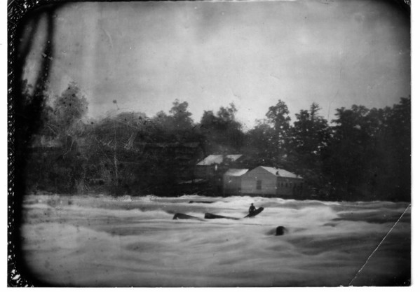 This picture shows part of the old Clark-Porter paper mill on old Bath Island, now Green Island. It was taken on a copper plate july 19, 1853, by P.D. Babbitt, from which plate it was copied by Orrin E. Dunlap. It shows Avery on the rock an log that notable day, when the entire population worked all day to rescue him with out success and he was swept over the American Falls about 5pm.