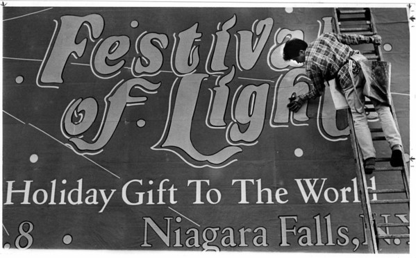 Christmas - Festival of Lights<br /> Penn Adv. Worker Joe Piazza of Buffalo - posts a sign about the Festival of Lights on a bill boardat 3rd Street and Duggan Drive.<br /> Photo - By Melissa Mahan - 11/26/1988.