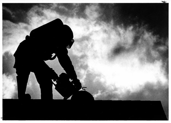 Fires- Niagara Falls<br /> Niagara Falls Firefighter Silhoutted against the evening sky, uses a saw to cut a hole in the roof while fighting a fire at 820 Pierce Ave.<br /> Photo - By Jamie Germano - 8/21/1987.