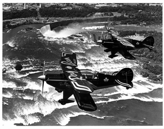 Airplanes - Airshow<br /> Ray Ban Gold acrobatic airplanes over Niagara Falls and the upper rapids.<br /> Photo - By Ron Schifferle - 7/15/1984.