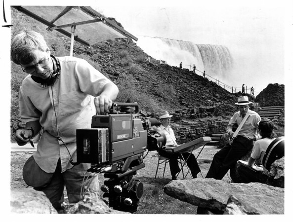Niagara Falls - Visitors<br /> Cameraman Gerry Langham.<br /> In Background from left to right:<br /> Paul Van Arsdale of North Tonawanda with his hammered dulcimer.<br /> David Holt - Host of sjow.<br /> Mike Alley - Director/Producer.<br /> Base of the Falls - for Nashville television net.<br /> Photo - By Holly Marvin - 5/23/1988.