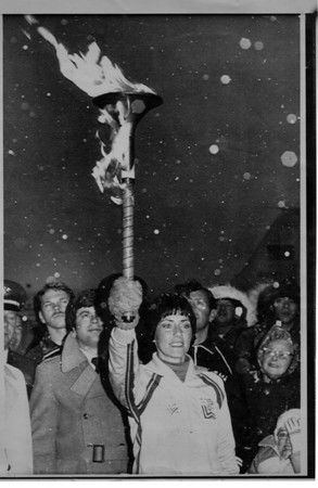 Olympics - lake Placid , N.Y.<br /> Langley Air Force Base Virginia. Snow falls heavily as Sandra Norris of Indiana holds the official Olympic Torch high above her head after it had arrived from Greece.  The Torch will be ran from Virginia to Lake Placid , N.Y. site of the 1980 Winter Olympic Games.<br /> January 31, 1980.